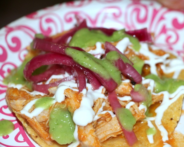 Chicken tinga tostadas with fresh green salsa and pickled red onions.